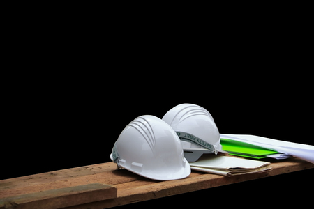 Plastic safety helmet and blueprint on wood isolated on black background and clipping path
