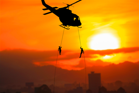 Photo for Silhouette Soldiers rappel down  to attack from helicopteron with sunset and copy space add text ( Concept stop hostilities To peace) - Royalty Free Image