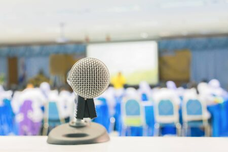 Close up microphone wireless Stand on white table in business conference interior seminar meeting room and Background blur