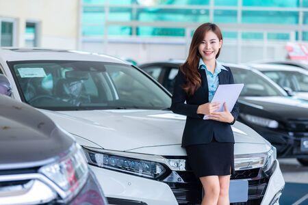 Photo pour Asian young woman in a car Rental Service Assistant/Car sales concept in show room. - image libre de droit