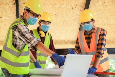 Photo pour Team of construction engineers and three architects are ready to wear medical masks. Coronavirus or Covid-19 wear masks during the design of construction. New normal - image libre de droit