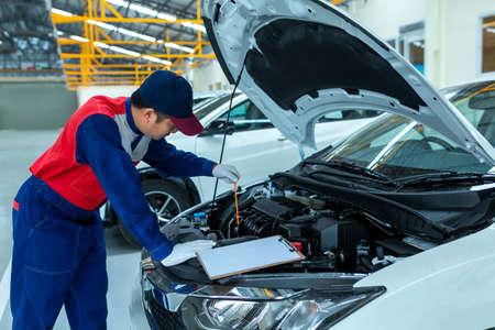 Photo pour Auto mechanic checking car engine oil in car auto repair service center. - image libre de droit