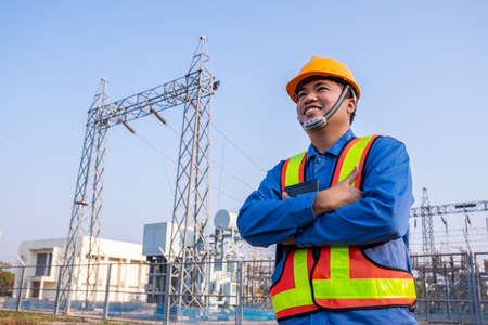 Photo for Asain electric engineer confident crossed arms and wear safety  in transmission station, Concept of electric power safety. - Royalty Free Image