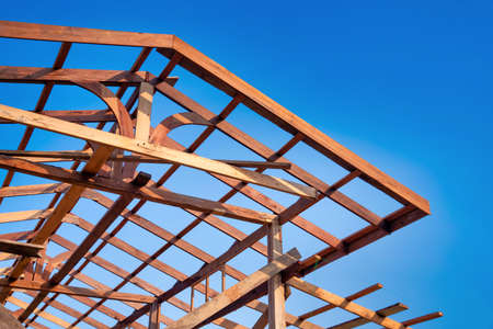 Photo for Wooden roof frame of a house against a blue sky. The frame of the cottage. The beginning of the construction of the house, Construction site. - Royalty Free Image