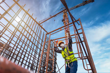 Photo pour Asian worker working on steel structure at height equipment constructive at construction site. Fall arrestor device for worker with hooks for safety body harness. - image libre de droit