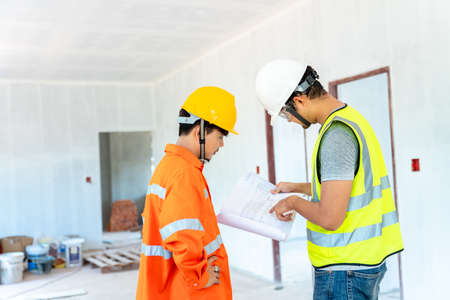 Photo pour Asian architect and engineer fiving instructions to his foreman on clipboard working at construction site - image libre de droit