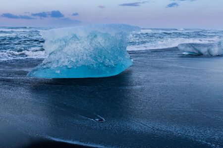 Ice breaking on black sand beach, Iceland winter season, natural landscape background
