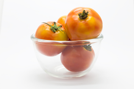 Fresh tomato on glass cup, on white background