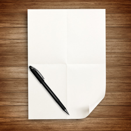 white paper with pen isolated on wood