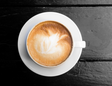 White cup of hot coffee latte on dark wooden table