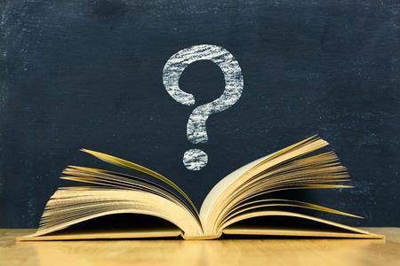 Photo pour Question mark symbol above vintage old book on blackboard background - image libre de droit