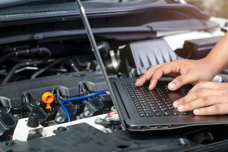 Photo for Detail of a mechanic using electrnoic diagnostic equipment to tune a car - Royalty Free Image
