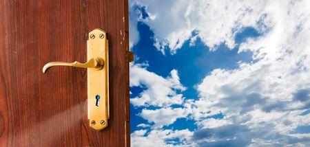 Open door against blue sky; opportunities, new beginning, launch, success, freedom concepts