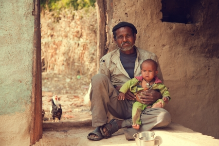 Indian poor father and son sitting on ground and he is holding his son