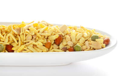 Aloo Mixture in a white ceramic oval bowl made with potatoes  peanuts  raisins  etc. Pile of Indian spicy snacks (Namkeen)  under backlight  side view  against the white background.の素材 [FY310163323745]