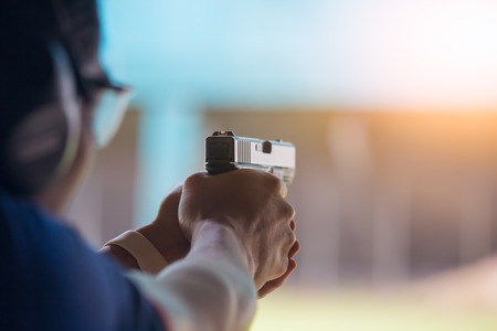 Photo for law enforcement aim pistol by two hand in academy shooting range in flare and vintage color - Royalty Free Image