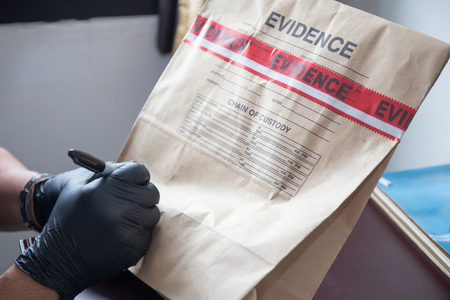 Photo pour forensic 's hand in black glove writing on evidence bag and seal by red tape in crime scene investigation - image libre de droit