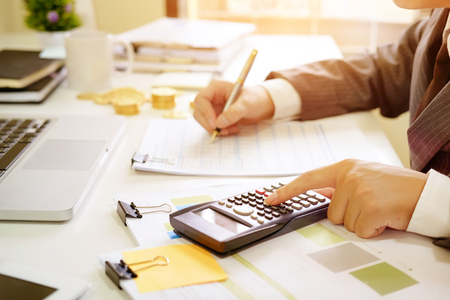 Close up business calculate finance data document paper with calculator.