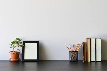 Foto de Workspace books, pencil, photo frame and bonsai on office desk. - Imagen libre de derechos