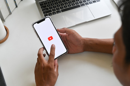 Foto de CHIANGMAI, THAILAND - MARCH 30, 2019: A man holds Apple iPhone XS Max open YouTube app on the screen, YouTube is the popular o sharing website. - Imagen libre de derechos