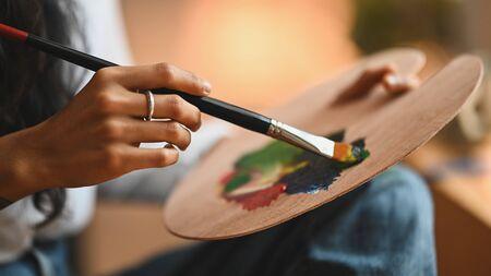 Foto de Cropped image of artist woman's hand drawing an oil color on canvas by paint brush at the modern art studio. Young artist/Painter concept. - Imagen libre de derechos