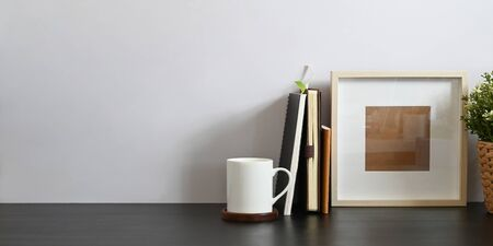 Photo pour Working desk along with book, notebook, picture frame, potted plant and coffee cup putting together on it with white cement wall as background. Orderly workspace concept. - image libre de droit