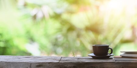 Photo pour Coffee morning concept, coffee cup with small dish putting on old plank together with stack of notebook over forest outside as background.  - image libre de droit