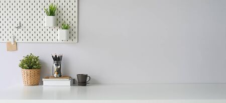 Photo pour Workspace that surrounded by coffee cup, diary, notebook, book, pencil holder, plant in wicker basket and potted plant. Orderly workplace concept. - image libre de droit