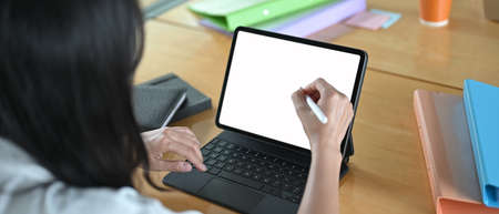 Photo pour Computer tablet with a white blank screen is putting on a working desk surrounded by various equipment. - image libre de droit