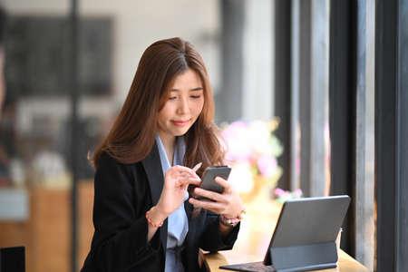 Foto de Successful businesswoman working with digital tablet while standing in modern office. - Imagen libre de derechos