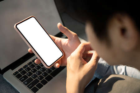 Photo pour Overhead shot of businessman holding horizontal smart phone with blank screen at his workplace. - image libre de droit