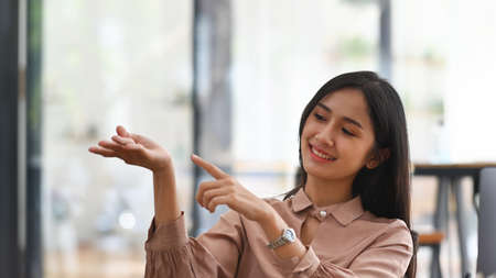 Photo pour Smiling asian businesswoman presenting and pointing something at copy space. - image libre de droit