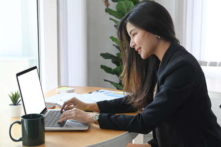 Photo for attractive businesswoman sitting with her colleague in office and making business call. - Royalty Free Image