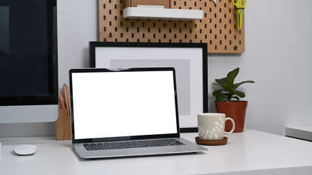 Photo pour Close up view mock up computer laptop with blank screen on white desk at home office. - image libre de droit