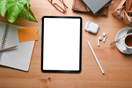 Photo for Overhead shot of modern workspace with digital tablet, wireless earphone, coffee cup and notebook on wooden table. - Royalty Free Image