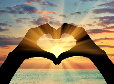 Photo pour Concept of feelings and emotions. Silhouette of the heart of the gesture of hands on background of sea sunset - image libre de droit
