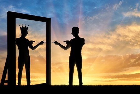 Photo pour Concept of a narcissistic and egoistic man. Silhouette of a man standing, motivating himself at the mirror and sees in the reflection of himself with a crown on his head - image libre de droit
