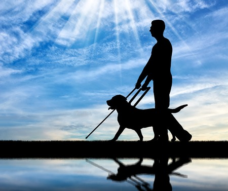 Silhouette of a blind disabled man follows a dog guide by the river with his reflection. The concept of blind people with guide dog