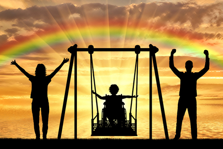 Photo pour Silhouette of happy child is disabled in a wheelchair on an adaptive swing with mom and dad on the background of a sea sunset with a rainbow. The concept of lifestyle of children with disabilities and their support - image libre de droit