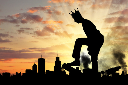 Foto de Big selfish man with a crown destroys the city on his way. Big Ego Concept - Imagen libre de derechos