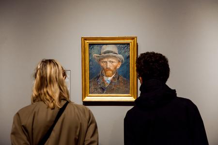 Foto de Visitors watching self-portrait artwork of famous painter Vincent van Gogh in Rijsmuseum in Amsterdam city, Holland - Imagen libre de derechos