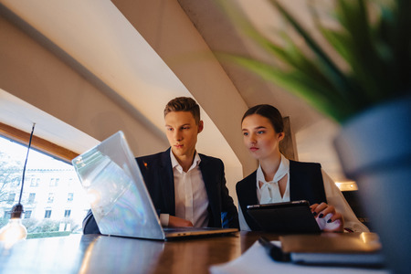 Photo for young businessmen boy and girl work with a laptop, a tablet and notes in the cafe with cozy interior - Royalty Free Image