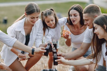 Photo pour picnic friends with pizza and drinks drinking and eating with cheers, warm sunny day, sunset, company, fun, couples and mom with baby - image libre de droit