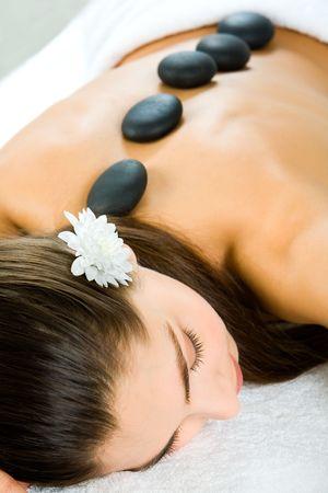 Attractive woman getting a stone massage in a spa