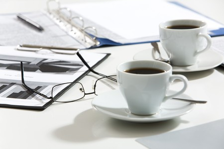 Close-up of glasses, documents, pen, cups of coffee on the table