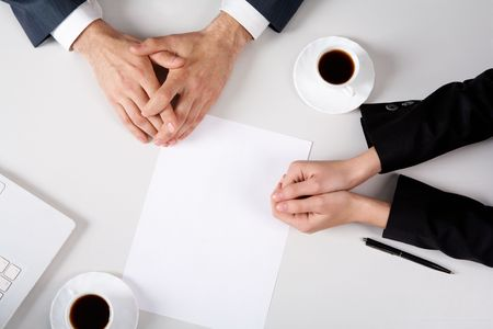 Above view of business people hands on workplace with blank paper near by