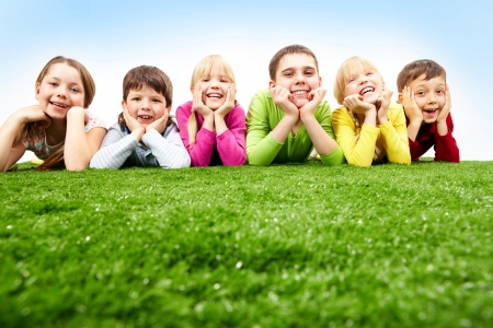 Image of happy boys and girls lying on a green grass