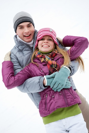 Portrait of happy couple in winter clothes looking at camera