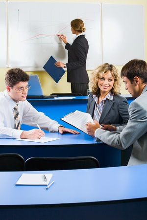 Group of people sitting at the blue table and discussing business questions in the class room