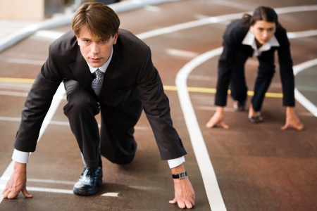 Businessman and businesswoman lined up getting ready for race in business